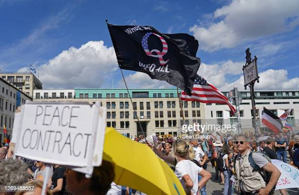 Man waves a QAnon conspiracy flag at a protest of coronavirus skeptics, right-wing extremists and others angry over coronavirus-related restrictions...
