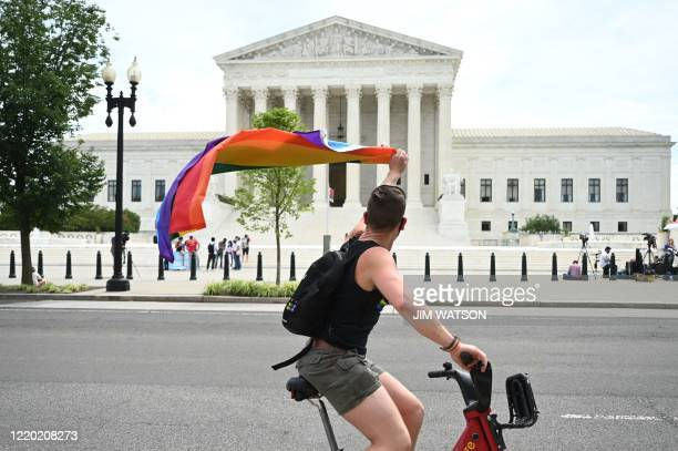 Man waves a rainbow flag as he rides by the US Supreme Court that released a decision that says federal law protects LGBTQ workers from...