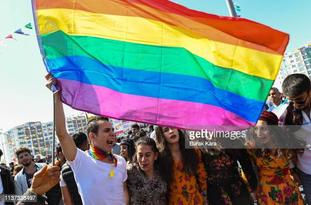 A man waves A rainbow flag as people dance and sing songs as they celebrate Nowruz festivities on March 21 2019 in Diyarbakir Turkey Nowruz marks the...
