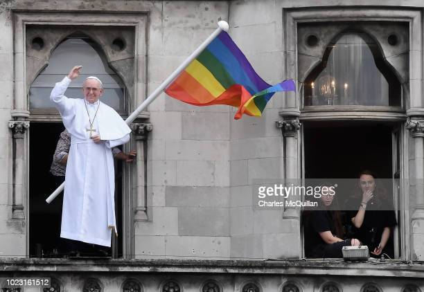 Man waves a rainbow flag behind a model of a pope which stands in the window above a bar as crowds wait for Pope Francis to travel through the city...