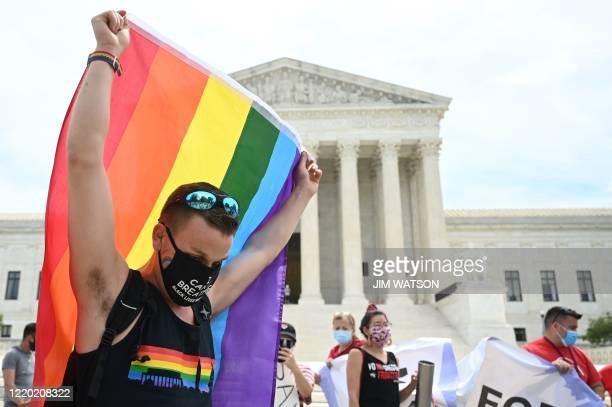 Man waves a rainbow flag in front of the US Supreme Court that released a decision that says federal law protects LGBTQ workers from discrimination...