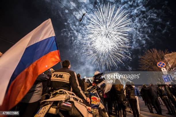 A man waves a Russian flag as people look at fire works in the center of the Crimean city of Simferopol on March 21 2014 Russia's upper house of...