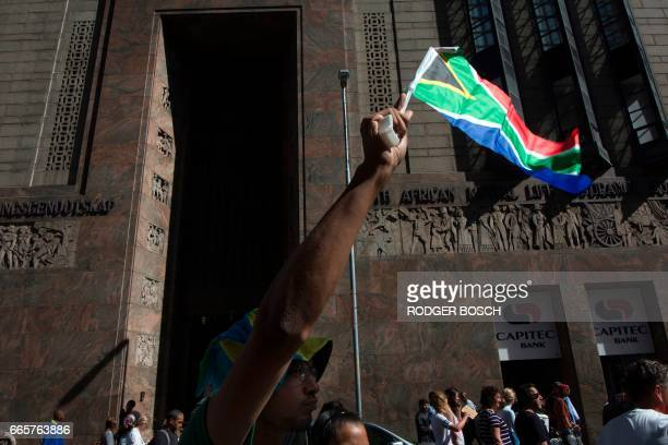A man waves a South Africa flag as thousands of people protest outside the South African Parliament waving South African flags and banners to call...