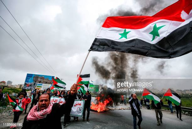 TOPSHOT A man waves a Syrian national flag as others wave Palestinian flags behind him while marching during a demonstration marking Land Day near...