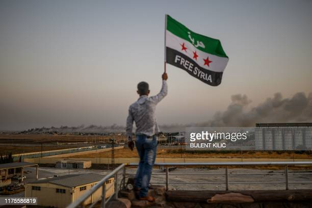 A man waves a Syrian opposition flag reading Free Syria on October 13 2019 in Akcakale as smoke rises in the background from the Syrian border city...