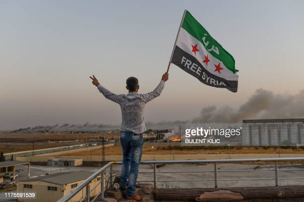 """Man waves a Syrian opposition flag reading """"Free Syria"""" on October 13, 2019 in Akcakale as smoke rises in the background from the Syrian border city..."""
