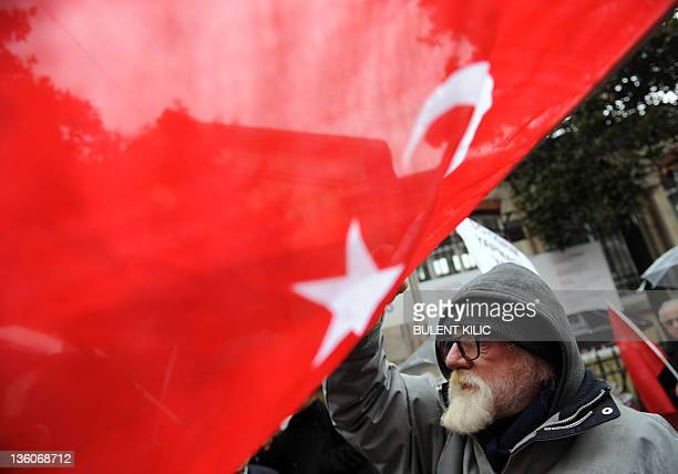 A man waves a Turkish flag as he takes part in a rally in front of the French Consulate in Istanbul on December 22 after the French Parliament...