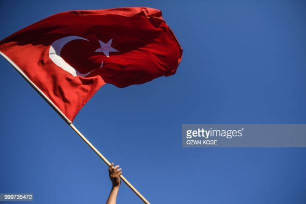 A man waves a Turkish flag as people take part in a rally near the 15 July Martyrs Bridge formerly called Bosphorus Bridge in Istanbul on July 15...