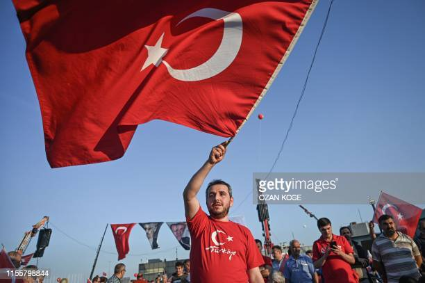 TOPSHOT A man waves a Turkish national flag as he takes part in a rally at the Ataturk International Airport in Istanbul on July 15 2019 for the...