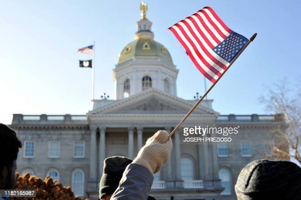 A man waves a US Flag as supporters cheer on Senator Elizabeth Warren as she speaks to them at a rally outside the New Hampshire State House after...