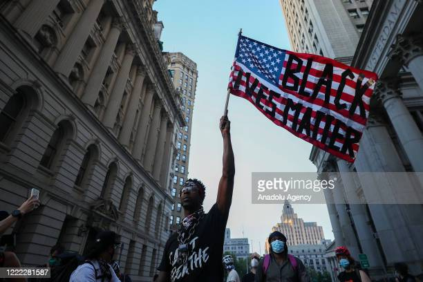 A man waves a US flag reading 'Black Lives Matter' during an antiracism protest in New York City United States on June 23 2020 The protestors have...