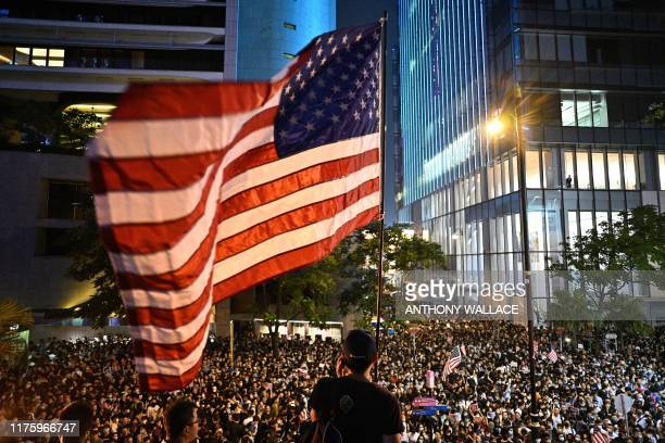 TOPSHOT A man waves a US national flag as protesters attend a rally in Hong Kong on October 14 calling on US politicians to pass a bill that could...