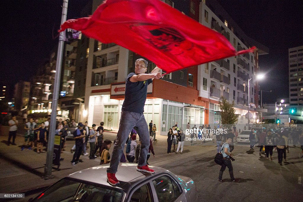 A man waves a wave from atop a car as people protest the upset election of Republican Donald Trump over Democrat Hillary Clinton in the race for President of the United States on November 9 2016 in Los Angeles, California, United States.