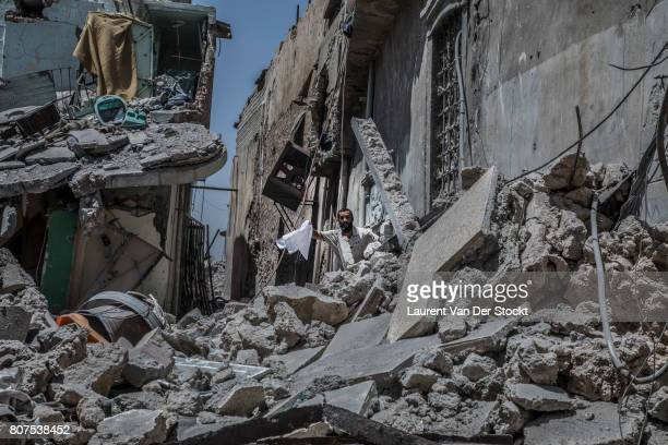 A man waves a white flag as he emerges from rubble in alNuri mosque complex in Mosul Iraq on June 29 2017 The Iraqi Army Special Operations Forces...