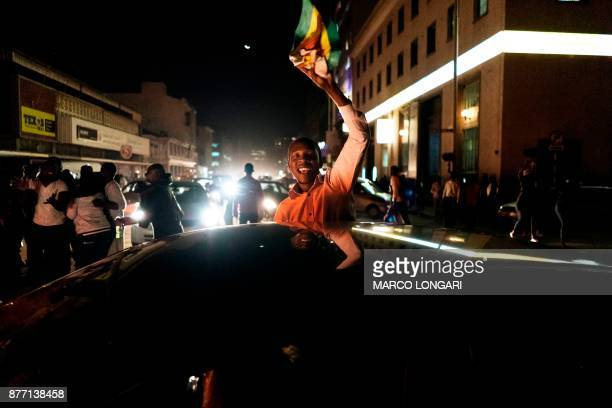 A man waves a Zimbabwean national flag as he celebrates with other citizens in the streets of Harare as the population celebrates after the...