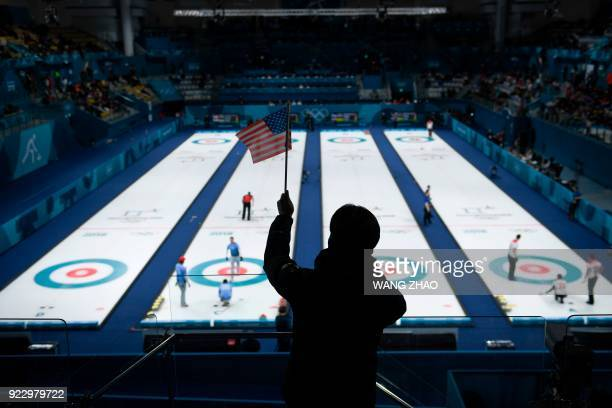 Man waves an American flag during the curling men's semi-final game between Canada and USA during the Pyeongchang 2018 Winter Olympic Games at the...