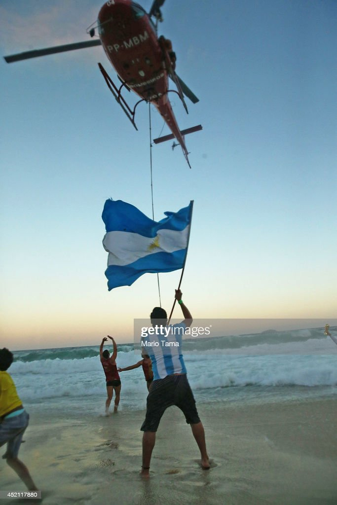 A man waves an Argentine flag as a Brazilian rescue helicopter departs after bringing a swimmer ashore off Copacabana Beach during the 2014 FIFA World Cup final match pitting Argentina against Germany on July 13, 2014 in Rio de Janeiro, Brazil. Germany won the match 1-0 in extra time at the famed Maracana stadium.
