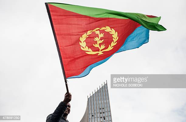 A man waves an Eritrean national flag as hundreds of Eritreans demonstrate in front of the African Union headquarters in support of the UN Inquiry...