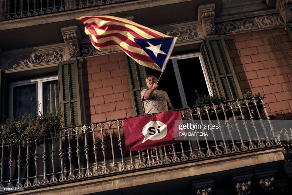 TOPSHOT - A man waves an 'Estelada' (Pro-independence Catalan flag) from a balcony after the closing of the 'Espai Jove La Fontana' (La Fontana youth center) polling station, on October 1, 2017 in Barcelona. Spanish riot police stormed voting stations today as they moved to stop Catalonia's independence referendum after it was banned by the central government in Madrid. At least 92 people were confirmed injured as hundreds tried to prevent the polling stations from being closed, Catalan officials said. A total of 465 people were treated at hospitals and health centres, while Spain's interior ministry said 12 police officers were injured. BARRENA