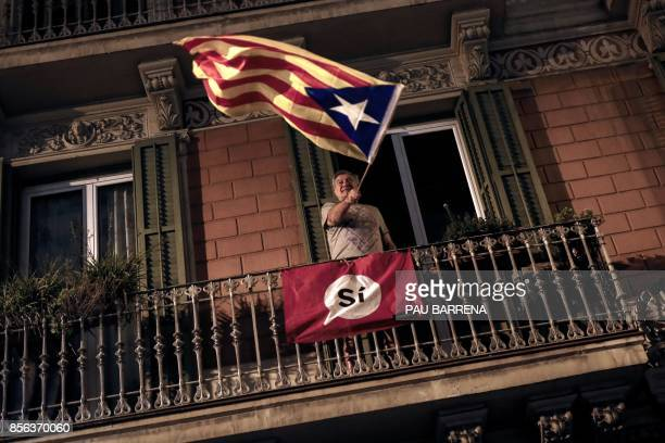 TOPSHOT A man waves an 'Estelada' from a balcony after the closing of the 'Espai Jove La Fontana' polling station on October 1 2017 in Barcelona...