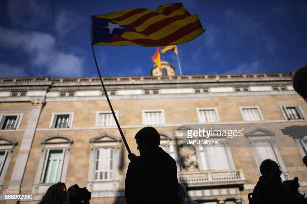 A man waves an independence flag outside the Palau Catalan Regional Government Building as Catalonia returns to work following last week's decision...