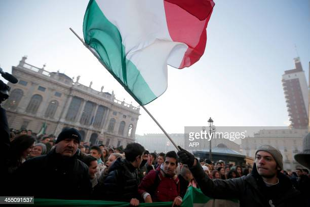 """Man waves an Italian national flag during a protest against austerity measures in """"Piazza Castello"""", in Turin on December 11, 2013. AFP PHOTO/MARCO..."""