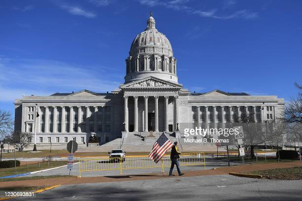Man waves and American flag as he walks outside the Missouri State Capitol building on January 20, 2021 in Jefferson City, Missouri. Supporters of...