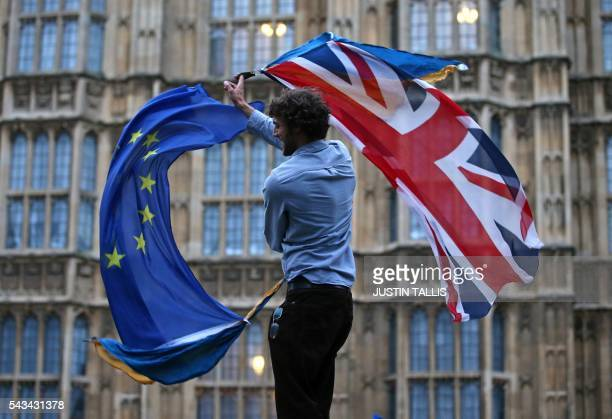 Man waves both a Union flag and a European flag together on College Green outside The Houses of Parliament at an anti-Brexit protest in central...