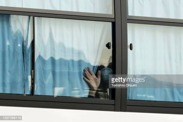Man waves from a bus carrying passengers who disembarked the quarantined Diamond Princess cruise ship as he leaves the Daikoku Pier on February 19,...