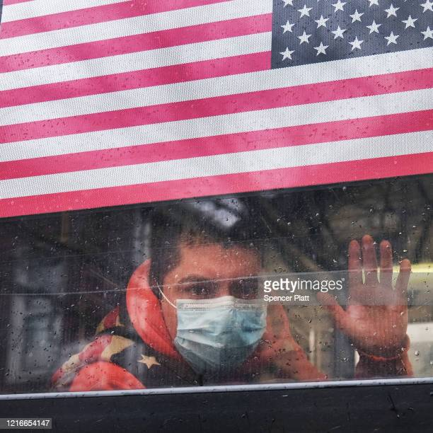 Man waves from a bus in a neighborhood in the Queens borough, which has one of the highest infection rates of coronavirus in the nation, on April 03,...