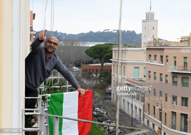 "Man waves from his balcony as part of a flash mob ""Un applauso per l'Italia"" at the Garbatella district in Rome on March 14 during the COVID-19..."
