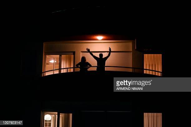 A man waves from his balcony in Pristina on March 20 2020 as measures are in place to attempt to prevent the spread of the COVID19 caused by the new...
