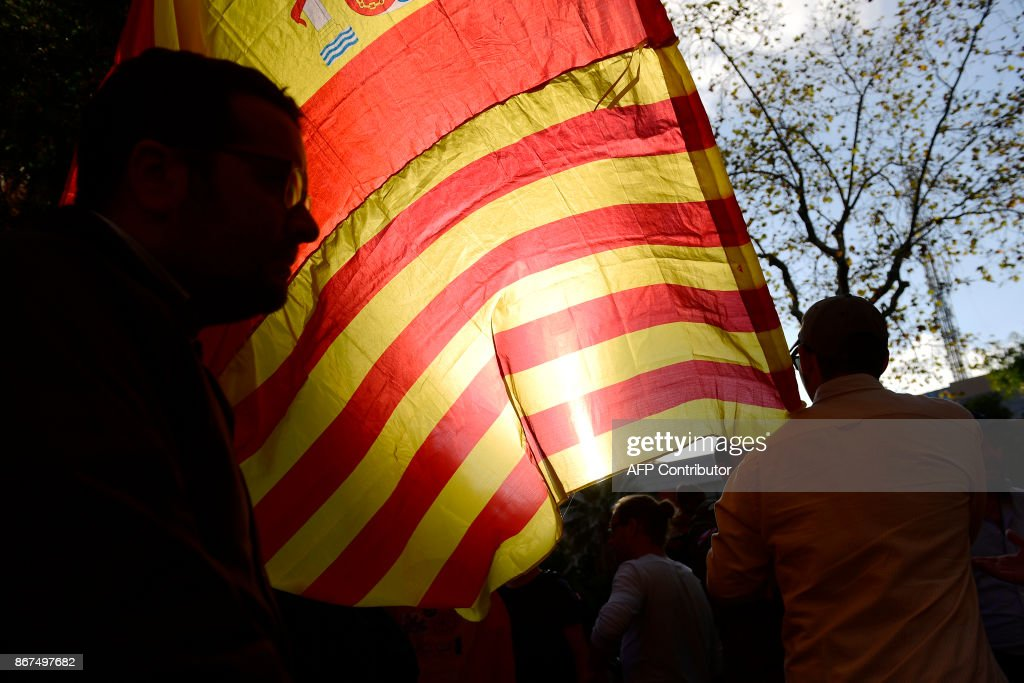 A man waves Spanish and Catalan flags during a demonstration calling for unity in Barcelona on October 28, 2017, a day after direct control was imposed on Catalonia over a bid to break away from Spain. Spain moved to assert direct rule over Catalonia, replacing its executive and top functionaries to quash an independence drive that has plunged the country into crisis and unnerved secession-wary Europe. /