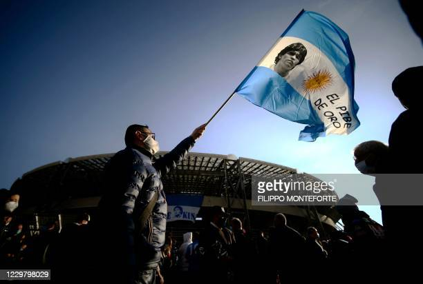 Man waves the flag of Argentina with a photo of late Argentinian football legend Diego Maradona, on November 26, 2020 outside the San Paolo stadium...