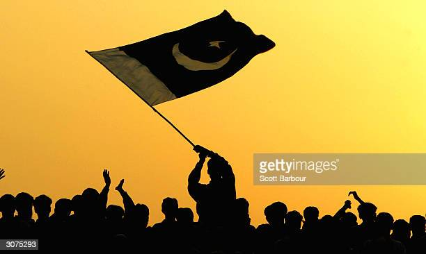 A man waves the flag of Pakistan in the air as people watch the ceremony to lower the national flags at the border crossing between Pakistan and...
