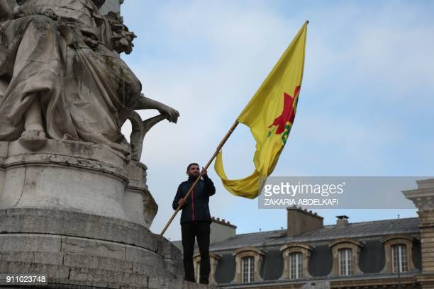 TOPSHOT A man waves the flag of the YPG during a demonstration against Turkey's military action in the Syrian town of Afrin part of Operation Olive...