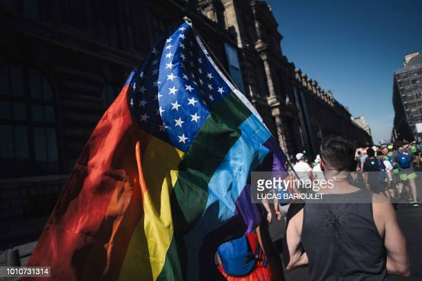 A man waves the rainbow flag as he takes part with others participants in the Rainbow Run from Paris City Hall to Place de la Concorde during the...