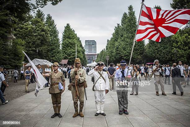 A man waves the Rising Sun flag right as others salute on arrival at the Yasukuni Shrine on the anniversary of Japan's World War II surrender in...