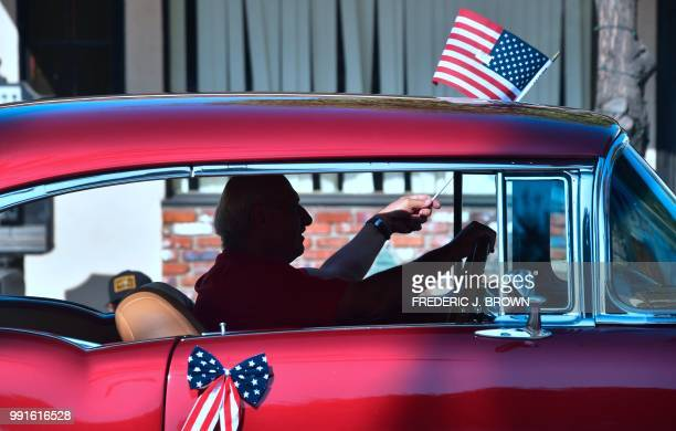A man waves the US flag while driving his classic car during a Fourth of July parade in San Gabriel California on July 4 2018 as cities and towns...