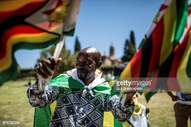 A man waves the Zimbabwean national flags as supporters of Tajamuka Sesijikisile SA The African Democrats Opposition Party the Zimbabwe Communist...