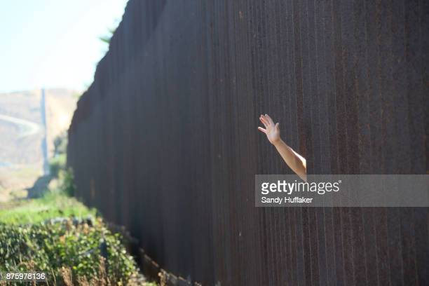 A man waves to family members through the US Mexico border November 18 2017 in San Ysidro California The event 'Abriendo La Puerta De La Espernaza'...