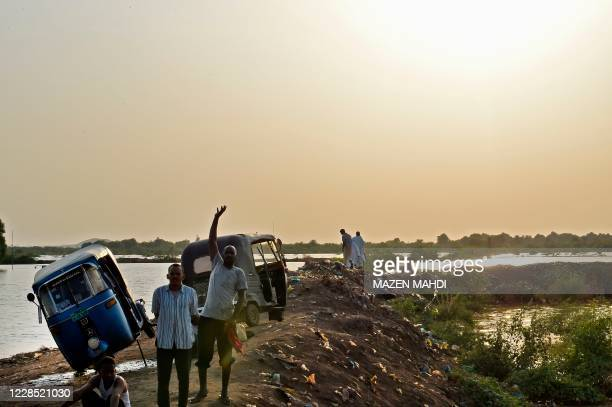 Man waves while standing next to tuk-tuks alongside other people by the flooded banks of the Nile river, on the outskirts of Sudan's capital Khartoum...