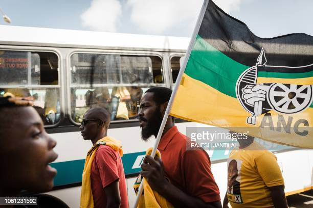 A man waving a flag of the ANC party walks past a bus transporting supporters as they all arrive at the African National Congress 107th anniversary...