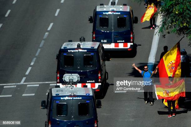 A man waving a Spanish flag gives the thumb up as Spanish Police van drive before a demonstration called by Societat Civil Catalana to support the...