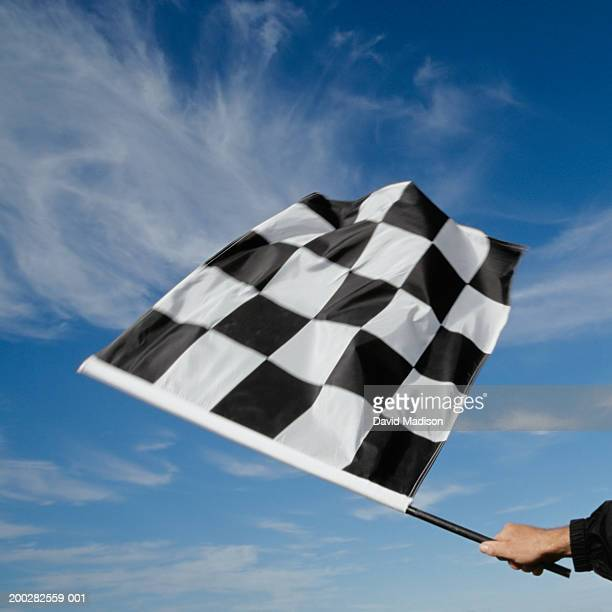 man waving checkered flag (blurred motion) - the end stock pictures, royalty-free photos & images