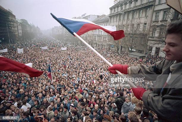 Man Waving Czech Flag Above Crowd