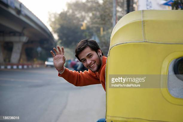 man waving from an auto rickshaw - auto rickshaw stock pictures, royalty-free photos & images