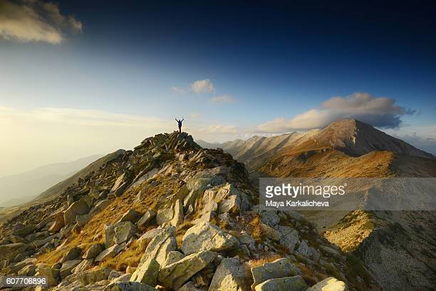 Man waving his hands on top of a mountain