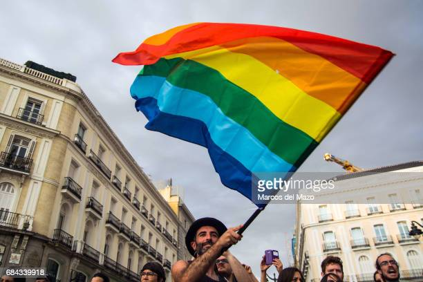 Man waving the rainbow flag during a demonstration for the International Day against Homophobia, Transphobia and Biphobia.