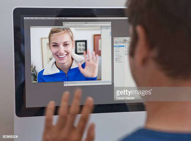 man waving to a woman on his computer screen - long distance relationship stock pictures, royalty-free photos & images